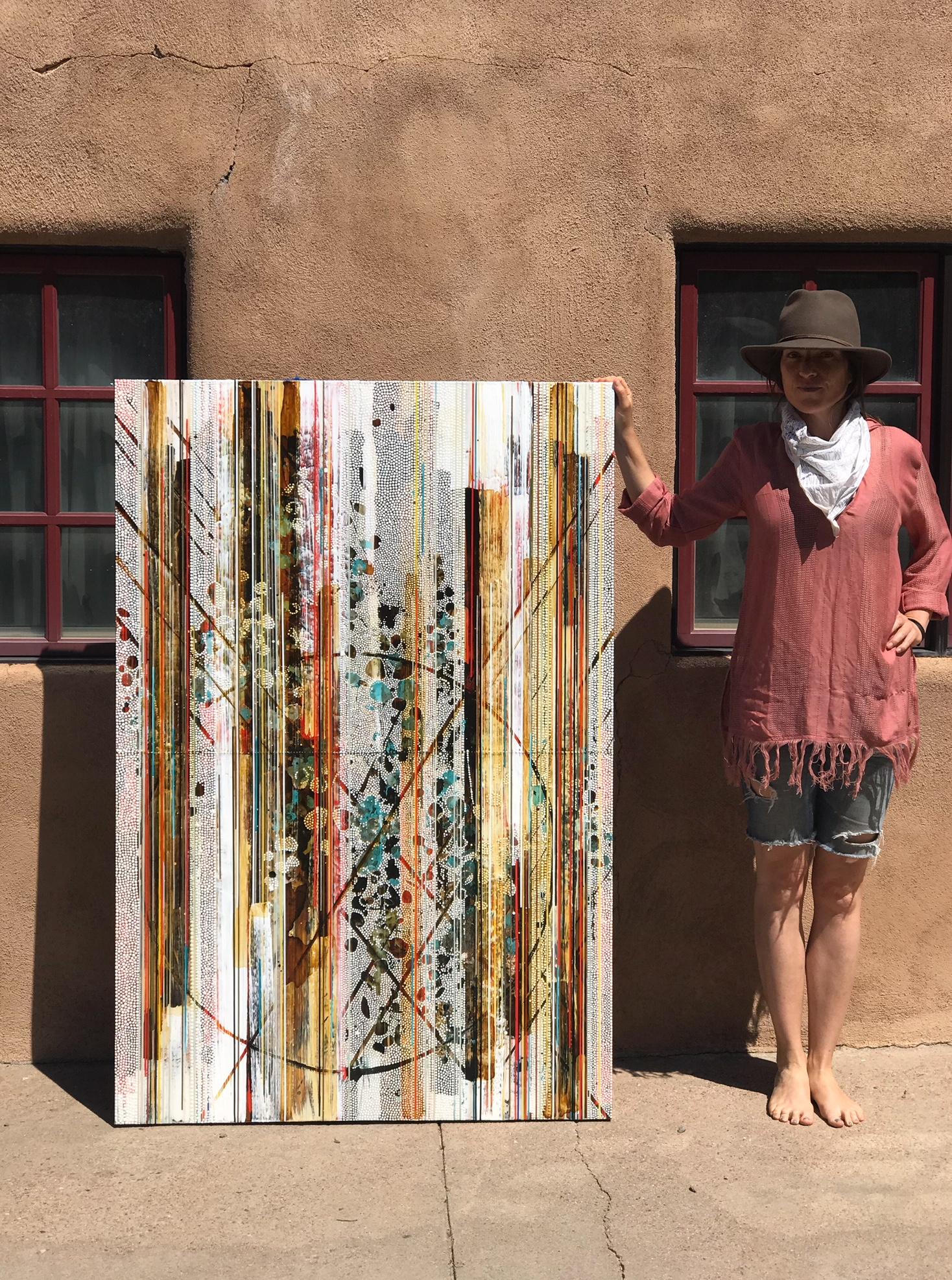 Outside her Santa Fe studio, Nina Tichava holds one of her works steady for the camera