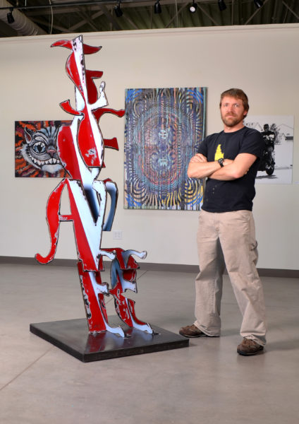Artist Joe Norman with his steel sculpture, Love/Fear""